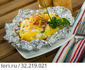 Купить «Baked in foil potatoes with filling of bacon, cheese and fried onion», фото № 32219021, снято 14 ноября 2019 г. (c) Яков Филимонов / Фотобанк Лори
