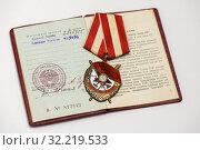 Орден Красного Знамени (орден «Красное знамя») на фоне удостоверения (2019 год). Редакционное фото, фотограф Игорь Низов / Фотобанк Лори
