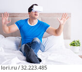 Купить «Young man in bed wearing a vr virtual reality head set», фото № 32223485, снято 24 мая 2017 г. (c) Elnur / Фотобанк Лори