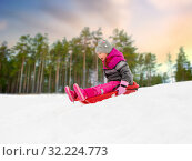 Купить «happy little girl sliding down on sled in winter», фото № 32224773, снято 10 февраля 2018 г. (c) Syda Productions / Фотобанк Лори