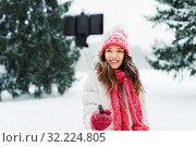 Купить «young woman taking selfie by monopod in winter», фото № 32224805, снято 29 января 2019 г. (c) Syda Productions / Фотобанк Лори