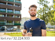 young sporty man with bottle outdoors. Стоковое фото, фотограф Syda Productions / Фотобанк Лори