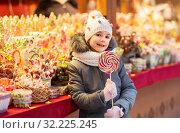 Купить «girl with lollipop at christmas market candy shop», фото № 32225245, снято 4 января 2019 г. (c) Syda Productions / Фотобанк Лори