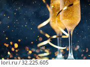 Two glasses of champagne with golden confetti, glitter, serpentine and lights. Стоковое фото, фотограф Евдокимов Максим / Фотобанк Лори