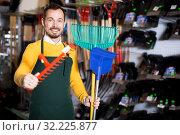 Купить «Seller displaying various items in garden equipment shop», фото № 32225877, снято 2 марта 2017 г. (c) Яков Филимонов / Фотобанк Лори