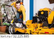 Купить «Young man is considering a lawnmower option», фото № 32225885, снято 2 марта 2017 г. (c) Яков Филимонов / Фотобанк Лори