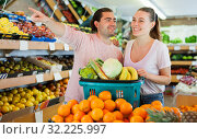 Купить «Family couple standing with full cart after shopping and pointing to shelves», фото № 32225997, снято 27 апреля 2019 г. (c) Яков Филимонов / Фотобанк Лори