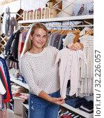 Купить «Woman showing baby costumes on hanger», фото № 32226057, снято 9 октября 2018 г. (c) Яков Филимонов / Фотобанк Лори