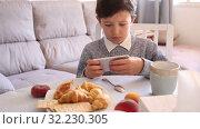 Купить «Teenager plays on smartphone in kitchen interior», видеоролик № 32230305, снято 12 июня 2019 г. (c) Яков Филимонов / Фотобанк Лори