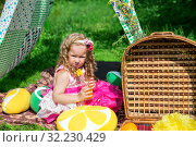 Smiling little girl with picnic basket sitting in meadow in a tent. Стоковое фото, фотограф Евгений Ткачёв / Фотобанк Лори