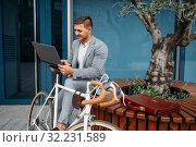 Businessman in suit with laptop and bike, downtown. Стоковое фото, фотограф Tryapitsyn Sergiy / Фотобанк Лори