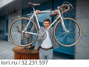 Strong businessman holds bicycle in downtown. Стоковое фото, фотограф Tryapitsyn Sergiy / Фотобанк Лори