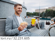 Businessman with cycle eats lunch on the bench. Стоковое фото, фотограф Tryapitsyn Sergiy / Фотобанк Лори