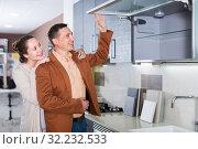 Купить «Smiling young customers choosing new kitchen», фото № 32232533, снято 4 апреля 2017 г. (c) Яков Филимонов / Фотобанк Лори