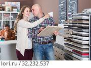 Купить «happy family couple looking at kitchen facade in furniture workshop», фото № 32232537, снято 4 апреля 2017 г. (c) Яков Филимонов / Фотобанк Лори