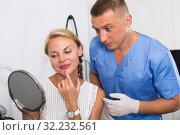 Купить «Female patient is analysing her skin with using mirror after the procedure», фото № 32232561, снято 7 августа 2017 г. (c) Яков Филимонов / Фотобанк Лори