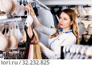 Female customer deciding on pretty bra. Стоковое фото, фотограф Яков Филимонов / Фотобанк Лори