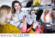 Купить «Female seller demonstrating client bras in underwear store», фото № 32232841, снято 20 марта 2017 г. (c) Яков Филимонов / Фотобанк Лори