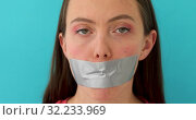 Female mouth taped. Woman wants to speak but it isn't allowed on blue background. Стоковое видео, видеограф Ekaterina Demidova / Фотобанк Лори