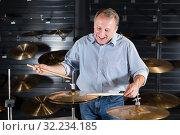 Купить «Man is playing on drum set», фото № 32234185, снято 18 сентября 2017 г. (c) Яков Филимонов / Фотобанк Лори