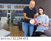 Купить «Couple holding samples of upholstery fabric», фото № 32234413, снято 29 октября 2018 г. (c) Яков Филимонов / Фотобанк Лори