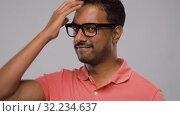 Купить «young indian man in glasses touching his hair», видеоролик № 32234637, снято 12 сентября 2019 г. (c) Syda Productions / Фотобанк Лори