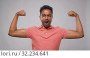 Купить «indian man showing biceps over grey background», видеоролик № 32234641, снято 12 сентября 2019 г. (c) Syda Productions / Фотобанк Лори