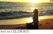 Купить «Yoga by sea and woman meditation in lotus position», видеоролик № 32236813, снято 25 сентября 2019 г. (c) Gennadiy Poznyakov / Фотобанк Лори