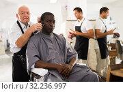 Купить «African man getting haircut from elderly barber», фото № 32236997, снято 22 августа 2019 г. (c) Яков Филимонов / Фотобанк Лори