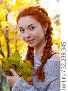 Девушка с рыжими волосами позирует на фоне желтых осенних листьев в парке. Стоковое фото, фотограф Момотюк Сергей / Фотобанк Лори