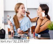 Young girl doing make-up for female friend at table with cosmetics. Стоковое фото, фотограф Яков Филимонов / Фотобанк Лори