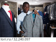 Купить «Afro-american man purchaser trying jacket in the dress shop», фото № 32240097, снято 16 октября 2019 г. (c) Яков Филимонов / Фотобанк Лори
