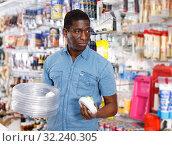 Купить «salesman arranging different goods on stand in shop», фото № 32240305, снято 21 января 2019 г. (c) Яков Филимонов / Фотобанк Лори