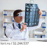 Купить «Young doctor looking at MRI scan through VR glasses», фото № 32244537, снято 17 мая 2017 г. (c) Elnur / Фотобанк Лори