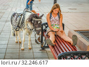 Russia, Orenburg, August 2016: the girl is the hostess of a pony, sitting on a bench, waiting for the children to ride the children on a pony on a sunny summer day. Редакционное фото, фотограф Акиньшин Владимир / Фотобанк Лори
