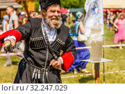 Купить «Russia, Samara, June 2016: the Cossack cuts a bottle with water for spectators of the festival on a sunny summer day. Traditional folk competitions in cabin by the Cossack draft.», фото № 32247029, снято 18 июня 2016 г. (c) Акиньшин Владимир / Фотобанк Лори