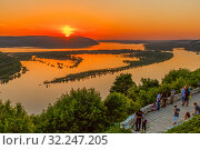 Russia, Samara, May 26, 2016: View of the Volga River from an observation platform near Samara, sunset over the Zhigulev mountains, spring flood of the river. The townspeople rest and admire the Volga. Редакционное фото, фотограф Акиньшин Владимир / Фотобанк Лори
