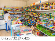 Купить «Russia, Saratov region, May 2016: showcase with a wide variety of products, food and drinks in a large village shop. The woman and the child pay at the cash desk for the goods. Text in Russian: coconut shaving.», фото № 32247425, снято 7 мая 2016 г. (c) Акиньшин Владимир / Фотобанк Лори
