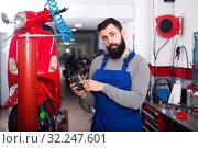 Beardy guy is calculating sum for repairing motorcycle. Стоковое фото, фотограф Яков Филимонов / Фотобанк Лори