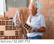 Купить «Man working with red brick», фото № 32247713, снято 19 июня 2018 г. (c) Яков Филимонов / Фотобанк Лори