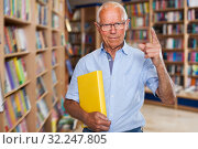 Купить «old-aged man in glasses standing in bookstore with book in his hands, pointing with his index finger up, recommending reading», фото № 32247805, снято 11 июня 2018 г. (c) Яков Филимонов / Фотобанк Лори