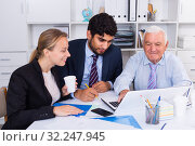 Купить «Office workers are writing financial reports», фото № 32247945, снято 27 июня 2017 г. (c) Яков Филимонов / Фотобанк Лори