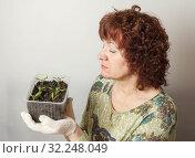 Купить «A female gardener shows a pot with sprouts after a pick.», фото № 32248049, снято 3 апреля 2016 г. (c) Акиньшин Владимир / Фотобанк Лори