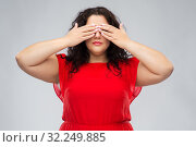 Купить «woman in red dress closing her eyes by hands», фото № 32249885, снято 15 сентября 2019 г. (c) Syda Productions / Фотобанк Лори