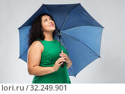 Купить «happy woman in green dress with blue umbrella», фото № 32249901, снято 15 сентября 2019 г. (c) Syda Productions / Фотобанк Лори