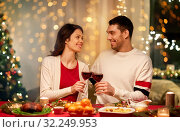 happy couple drinking red wine at christmas dinner. Стоковое фото, фотограф Syda Productions / Фотобанк Лори