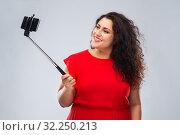 Купить «woman taking picture by smartphone on selfie stick», фото № 32250213, снято 15 сентября 2019 г. (c) Syda Productions / Фотобанк Лори