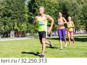 Купить «happy young sportsmen racing wit badge numbers», фото № 32250313, снято 16 августа 2015 г. (c) Syda Productions / Фотобанк Лори