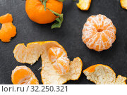 Купить «close up of peeled mandarins on slate table top», фото № 32250321, снято 5 апреля 2018 г. (c) Syda Productions / Фотобанк Лори