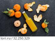 Купить «glass bottle of fruit juice and peeled mandarins», фото № 32250329, снято 5 апреля 2018 г. (c) Syda Productions / Фотобанк Лори